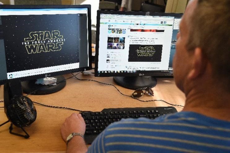 "A man looks at a tweet announcing the completion of filming and the title for the newest ""Star Wars"" film, on November 6, 2014 in Hollywood, California"
