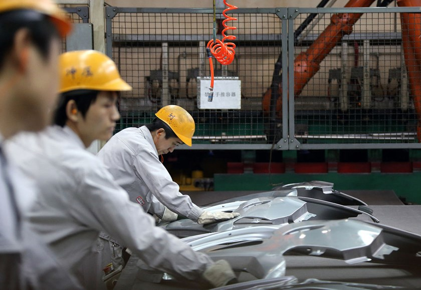 Workers inspect components for vehicles on the production line at a plant operated by Dongfeng Peugeot-Citroen Automobile Ltd. in Wuhan, China.