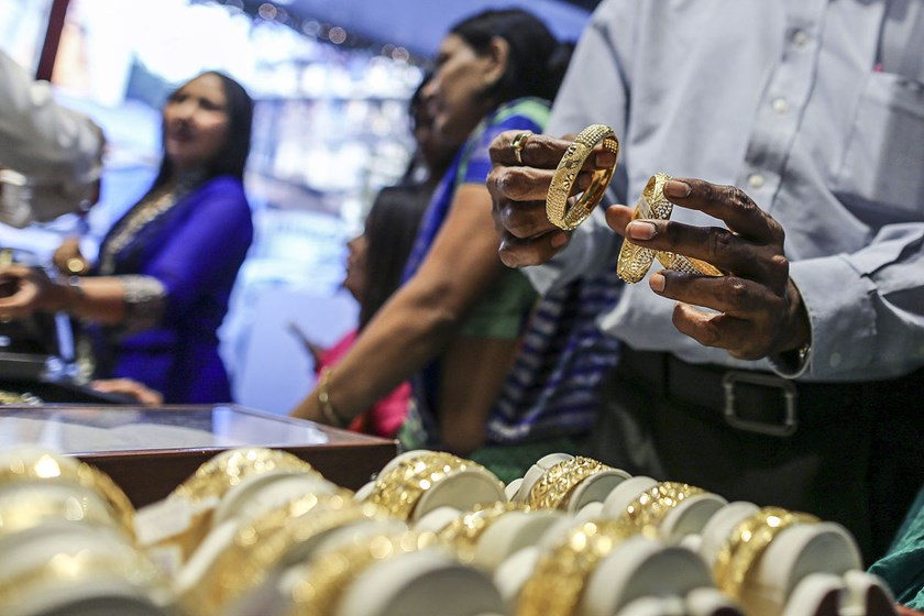 A customer inspects gold bangles at the Umedmal Tilokchand Zaveri jewelry store in the Zaveri Bazaar area of Mumbai, India.