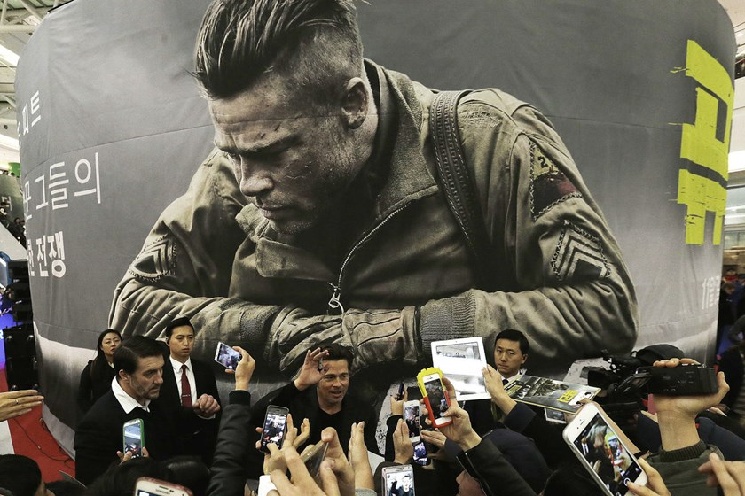 "Actor Brad Pitt, background center, waves to fans during a promotional event for his latest film ""Fury"" in Seoul, South Korea, on Nov. 13, 2014."
