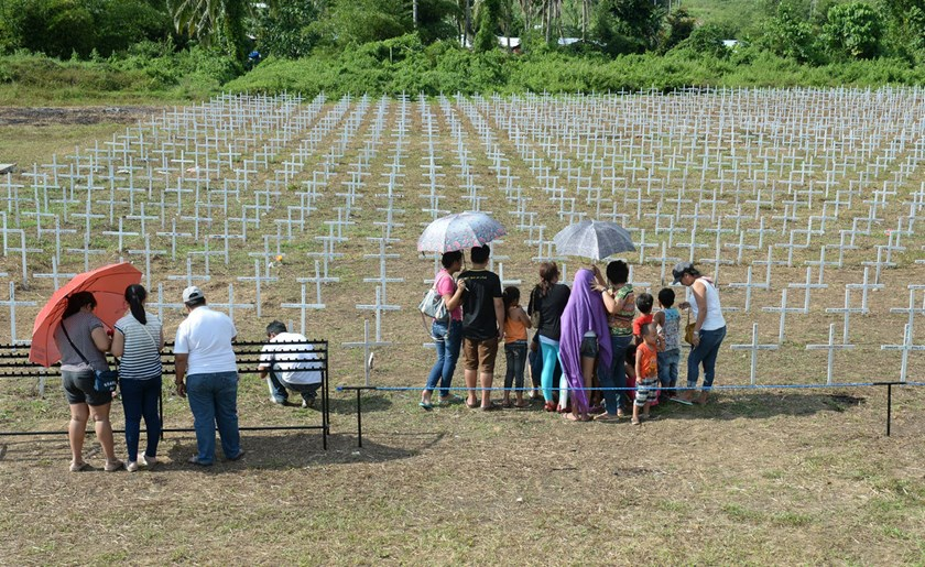 Relatives of victims of super Typhoon Haiyan, visit the mass grave as they offer prayers for their loved ones at Vasper village in Tacloban City, in central Philippines on Nov. 7, 2014, a day before the first year anniversary of the devastating typhoon.