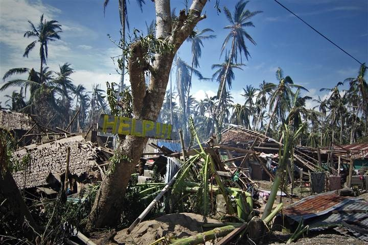 Destroyed houses and trees with a slogan calling for help in the village of Mantang in Samar province on Monday. Photo: AFP