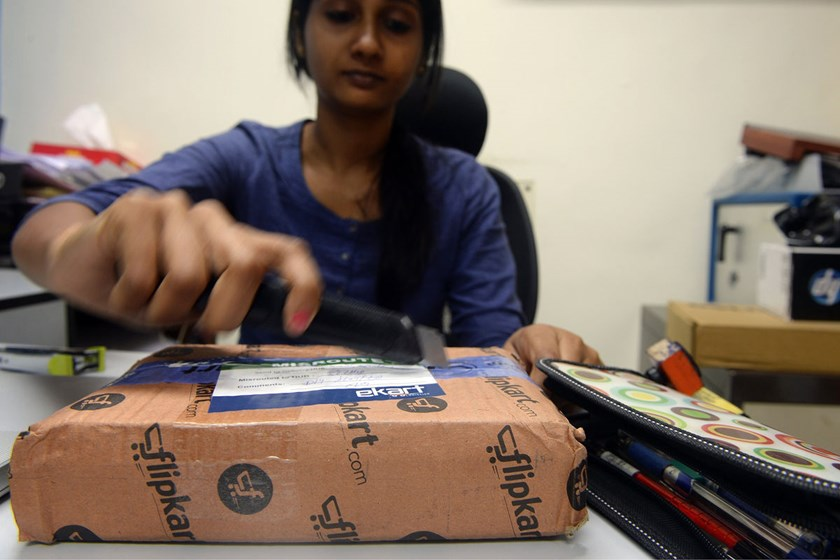 A woman opens a parcel in her office after ordering it from an online shopping website in Mumbai, India.