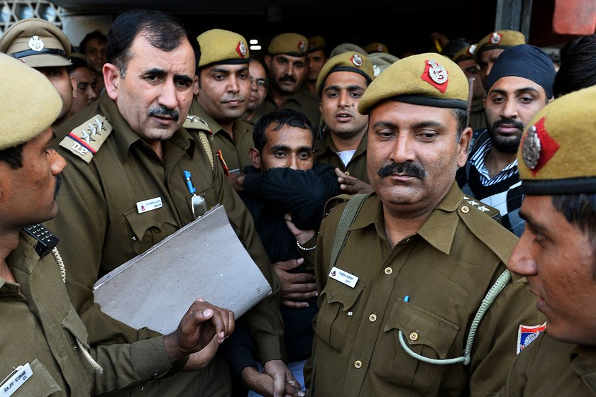 Indian police escort Uber taxi driver and accused rapist Shiv Kumar Yadav, center, following his court appearance in New Delhi on Dec. 8, 2014.