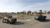 Military vehicles of Iraqi security forces make their way on the outskirts of Baiji, north of Baghdad December 8, 2014.