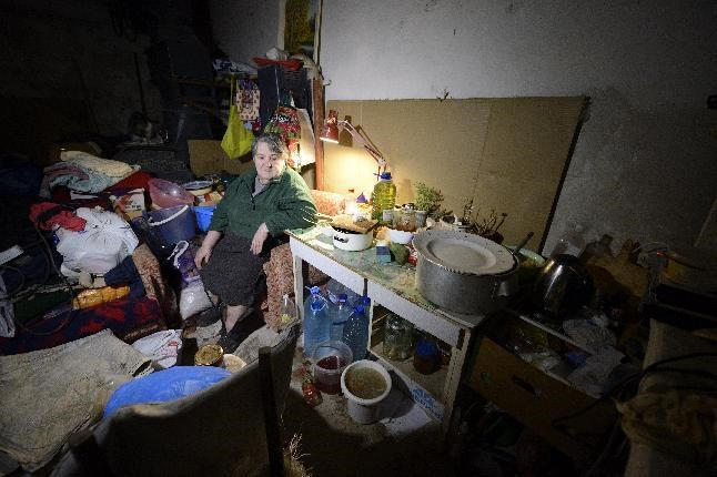 A woman takes shelter in the cellar of her building in Kievskiy district, which is often shelled, in the pro-Russian rebel-controlled eastern Ukrainian city of Donetsk, on December 10, 2014