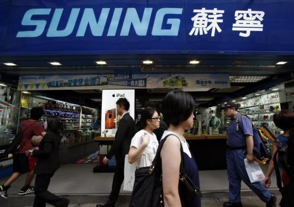 People walk past a Suning store, one of the largest home appliance retailers in China, in Hong Kong August 26, 2013.