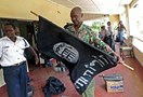A Kenyan police officer folds up a flag inscribed with the logo of the Islamic state (IS) following a raid on two mosques in the coastal city of Mombasa, on November 17, 2014