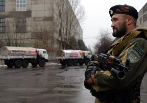 "A supporter of the self-proclaimed ""People's Republic of Donetsk"" stands guard as a Russian convoy carrying humanitarian aid for the eastern Ukrainian Donetsk region approaches the city of Makiyivka near Donetsk, on December 12, 2014"