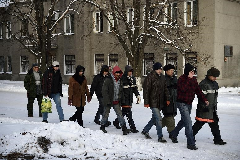 "Ukrainian prisoners from the ""Donbass"" bataillon followed by Donetsk People's Republic (DNR) rebel guard, walk in a street of the eastern Ukrainian city of Ilovaisk, controlled by pro-russian rebels, on December 4, 2014"