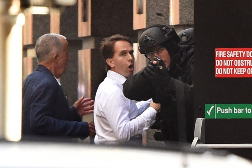 Two hostages, left, run for cover behind a policeman, right, during a hostage siege in the central business district of Sydney on Dec. 15, 2014.