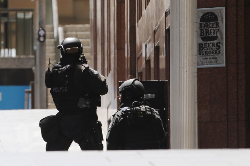 Police stand at the ready close to a cafe under siege in Martin Place in the central business district of Sydney, Australia, Monday, Dec. 15, 2014.