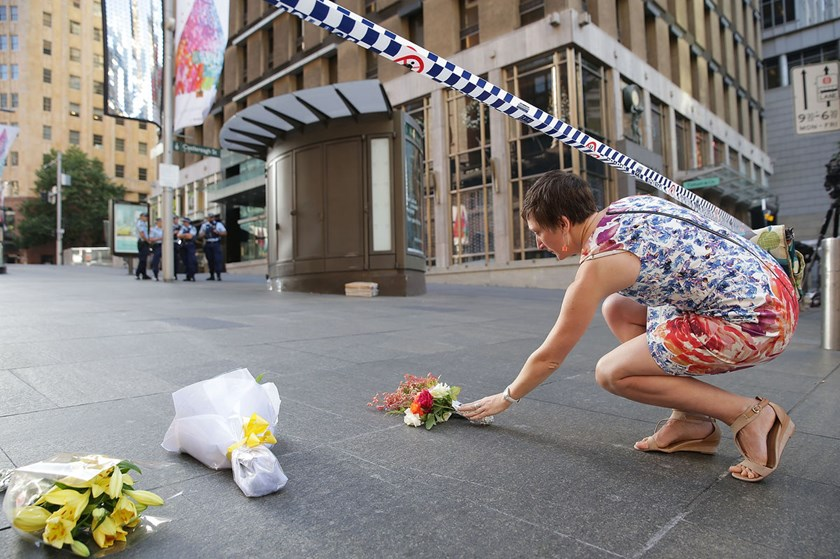 A woman cries as she leaves flowers to pay her respects at Martin Place in Sydney, Australia, on Dec. 16, 2014.