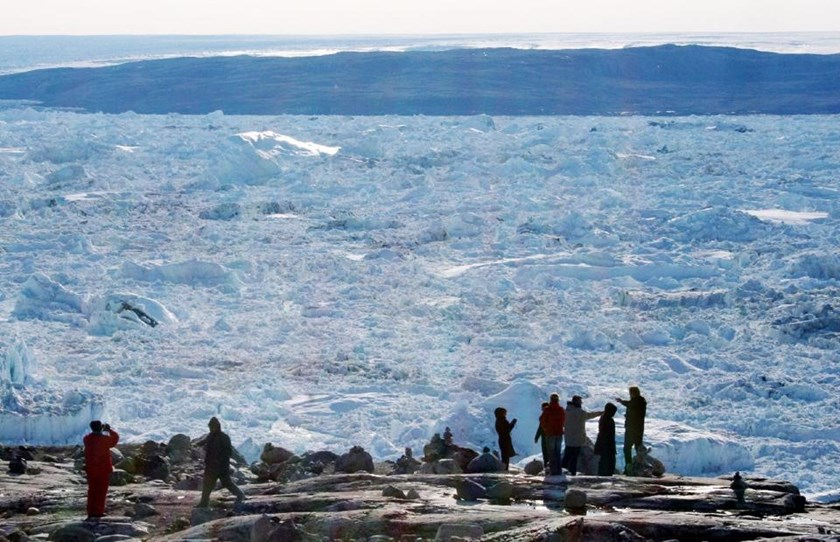 Tourists look out over the ice of the Ilulissat fjord on September 11, 2008 in Ilulissat, on the western coast of Greenland
