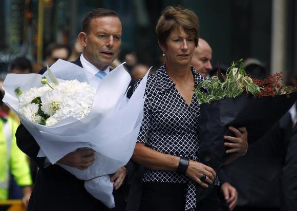 Australian Prime Minister Tony Abbott and his wife Margie prepare to place floral tributes near the cafe in central Sydney December 16, 2014 where hostages were held for over 16-hours.