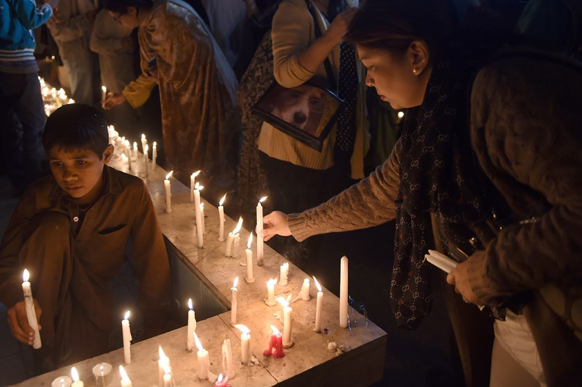 Activists of Pakistan Tehreek e Insaaf (PTI) light candles for the victims of an attack by Taliban gunmen on a school in Peshawar, in Karachi on Dec. 16, 2014.