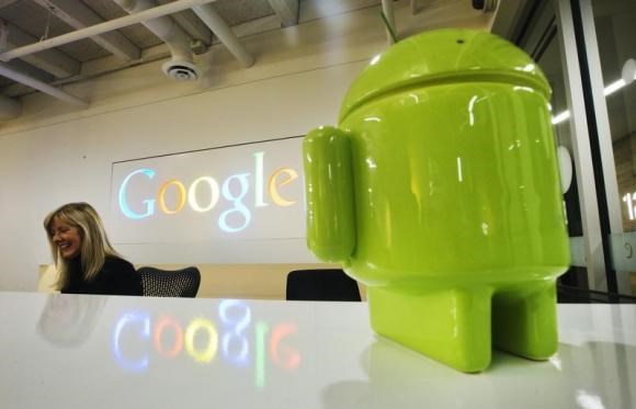 A Google Android figurine sits on the welcome desk as employee Tracy McNeilly smiles at the new Google office in Toronto, November 13, 2012.