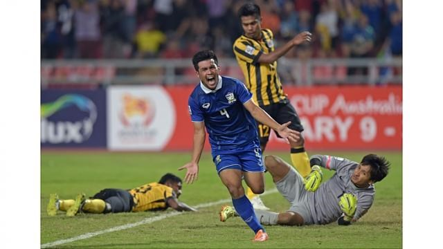 Kroekrit Thawikan of Thailand (centre) celebrates after scoring against Malaysia during their final 1st leg football match of the Suzuki Cup 2014 at the Rajamangala stadium in Bangkok on Dec 17, 2014. Photo: AFP