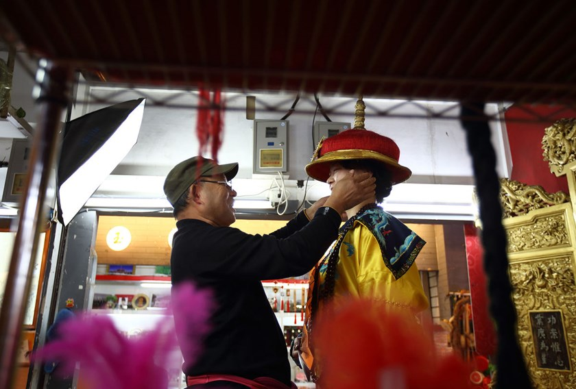 A photographer helps a customer wear a traditional Chinese rental costume at a photo shop in Beijing, China. The economic census is conducted about every five years to gather information on the manufacturing and services industries.