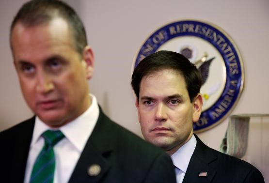 Senator Marco Rubio, (R-FL), (R) listens to Rep. Mario Diaz-Balart, (R-FL), during a press conference in Miami, Florida December 18, 2014.