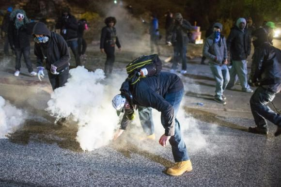 A protester reaches for a tear gas canister during a second night of protests in Ferguson, Missouri November 25, 2014.
