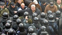 A protester argues with police in front of Ukrainian Parliament in Kiev on December 23, 2014 as lawmakers adopt a bill dropping Ukraine's non-aligned status