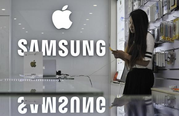 A sales assistant uses her mobile phone next to the company logos of Apple and Samsung at a store in Hefei, Anhui province in this September 10, 2014 file photo.