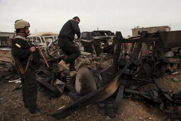 Kurdish Peshmerga fighters stand near burning vehicles during a suicide attack carried out by the Islamic State group in Kesarej village, south of Zumar, Nineveh province December 18, 2014.