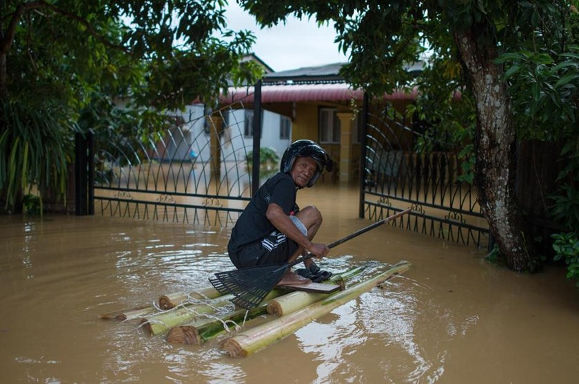A man uses a makeshift raft to make his way to his house submerged in floodwaters in Pengkalan Chepa, near Kota Bharu on December 27, 2014