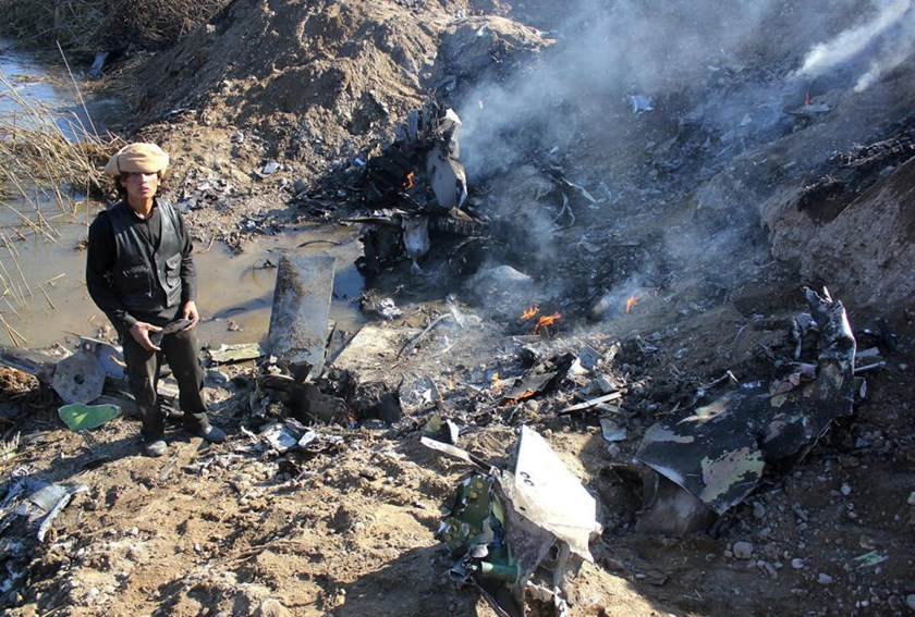 A picture taken on December 24, 2014 reportedly shows an Islamic State group fighter collecting pieces from the remains of a Jordanian warplane in Syria's Raqa region