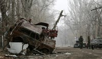 Pro-Russian separatists stand guard next to cars damaged during fighting between pro-Russian rebels and Ukrainian government forces near Donetsk Sergey Prokofiev International Airport, eastern Ukraine, December 16, 2014.