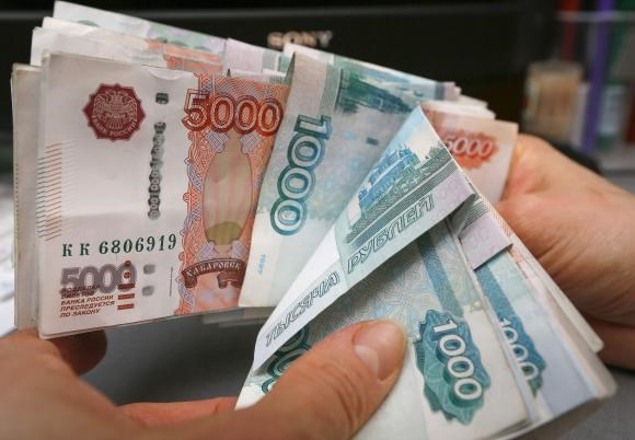 An employee counts Russian ruble banknotes at a small private shop selling home appliances in Krasnoyarsk December 26, 2014.