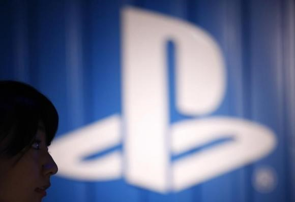 The logo of Sony Corp's PlayStation is seen next to a woman at its booth during the Tokyo Game Show 2014 in Makuhari, east of Tokyo September 18, 2014.