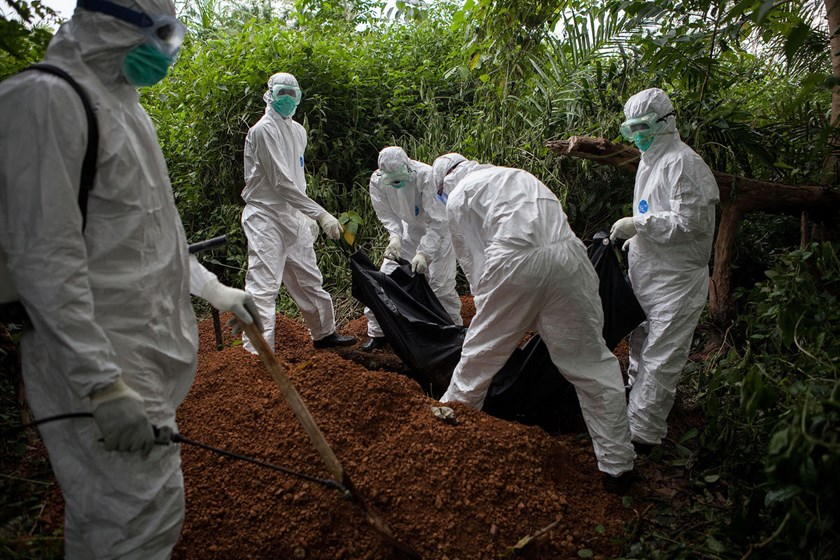 A specialized Ebola inhumation team bury the body of a recent Ebola victim in Magbonkoh, Sierra Leone, on Oct. 6, 2014.