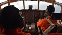 Indonesian Air Force personnel fly a C-130 Hercules aircraft over the Java Sea during search and rescue operations for missing AirAsia flight QZ8501 on Dec. 29, 2014.