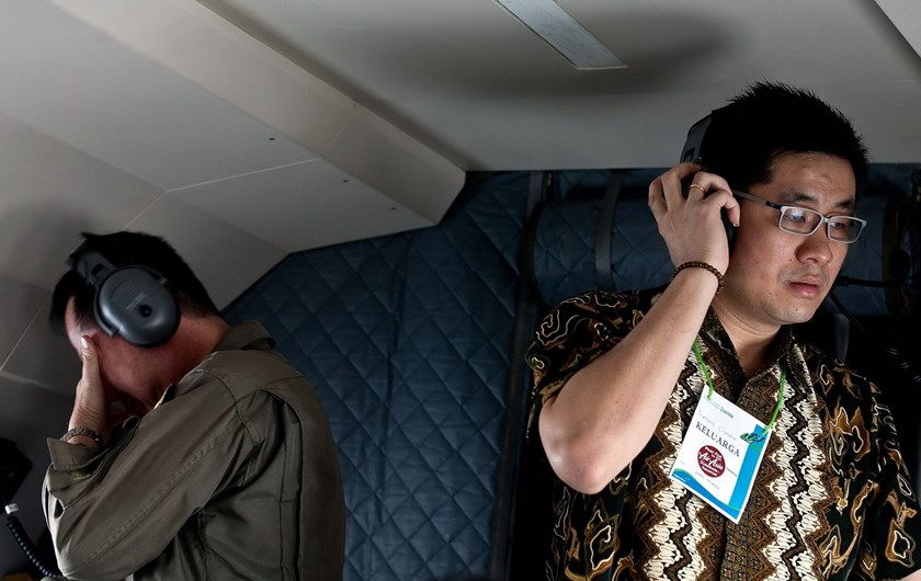 Family member of passengers onboard the missing Malaysian air carrier AirAsia flight QZ8501, accompany Indonesian military personnel on a search and rescue (SAR) mission over the waters of the Java Sea on December 30, 2014. Photo: AFP
