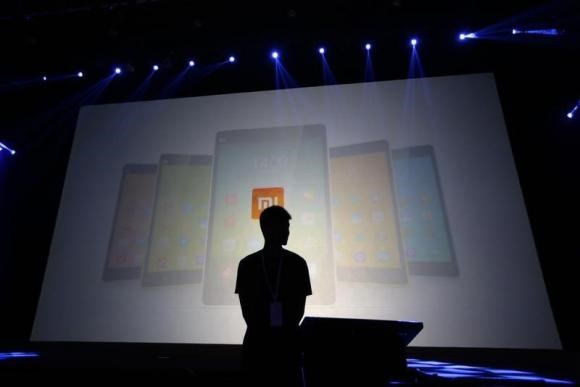 A security guard stands in front of a screen showing Xiaomi mobile phones ahead of the launching ceremony of Xiaomi Phone 4, in Beijing, July 22, 2014.