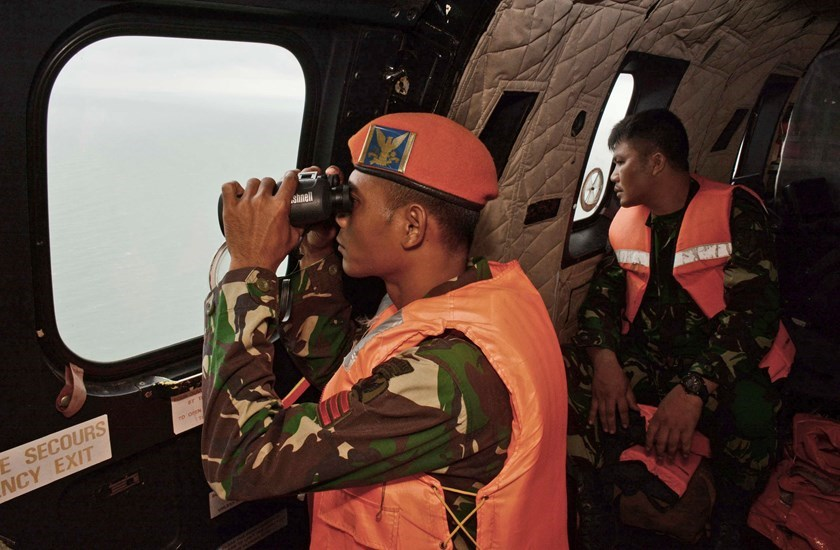 A crewmember of an Indonesian Air Force Super Puma helicopter of 6th Air Squadron uses a binocular to scan the horizon during a search operation for the victims of AirAsia Flight QZ 8501 over the Java Sea January 1, 2015. Photo credit: Reuters