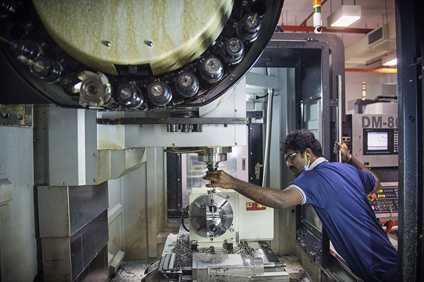 An employee calibrates a precision drilling machine at the Coway Engineering & Marketing Pte. manufacturing facility in Singapore. The nation's manufacturing fell 5.8 percent last quarter from the previous three months, the trade ministry said.