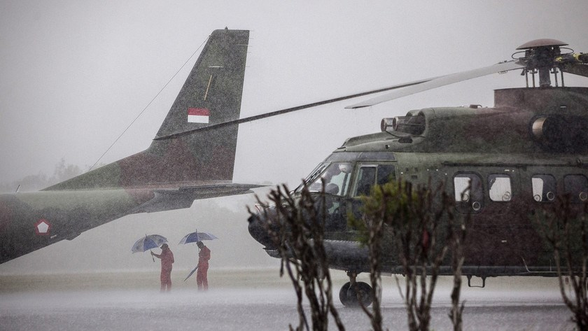 Two Indonesian military crew wait for rain to ease under the tail of a military plane at Iskandar airbase, as bad weather slows down the search for victims and debris of the AirAsia flight QZ8501 crash today in Pangkalan bun, Indonesia.