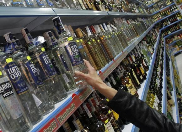 A customer takes a bottle of vodka from a shelf at a Russian supermarket in Benidorm, November 26, 2012.