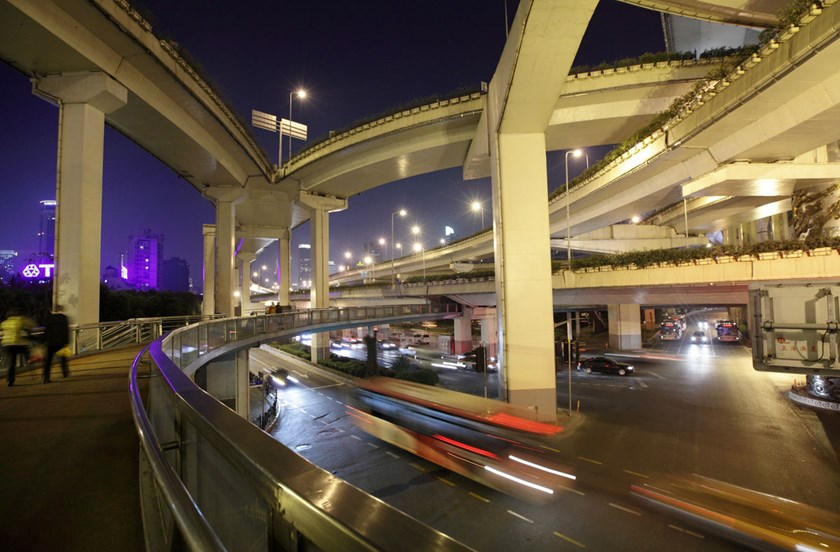 Traffic moves under elevated roads at night in Shanghai, China.