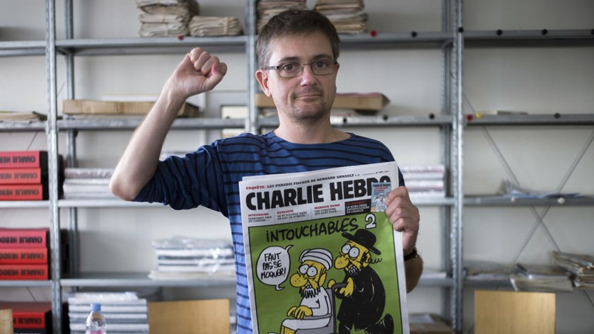 French satirical weekly Charlie Hebdo's cartoonist and editor-in-chief Stephane Charbonnier, known as Charb, clenches his fist in the paper's office in Paris, on Sept. 19, 2012.