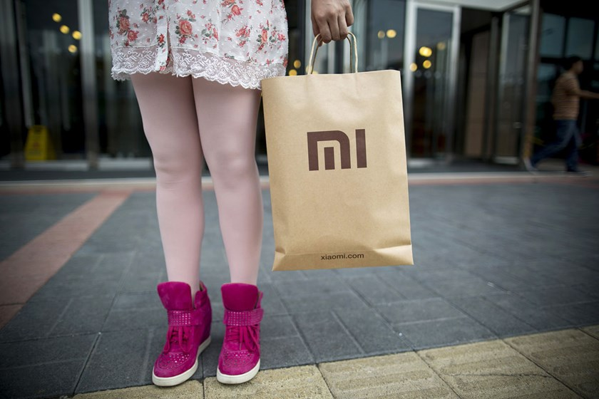 A Xiaomi Corp. employee holds a Xiaomi-branded shopping bag outside the company's offices in Beijing.