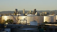 Oil storage tanks are seen at sunrise with the Rocky Mountains and the Denver downtown skyline in the background October 14, 2014.