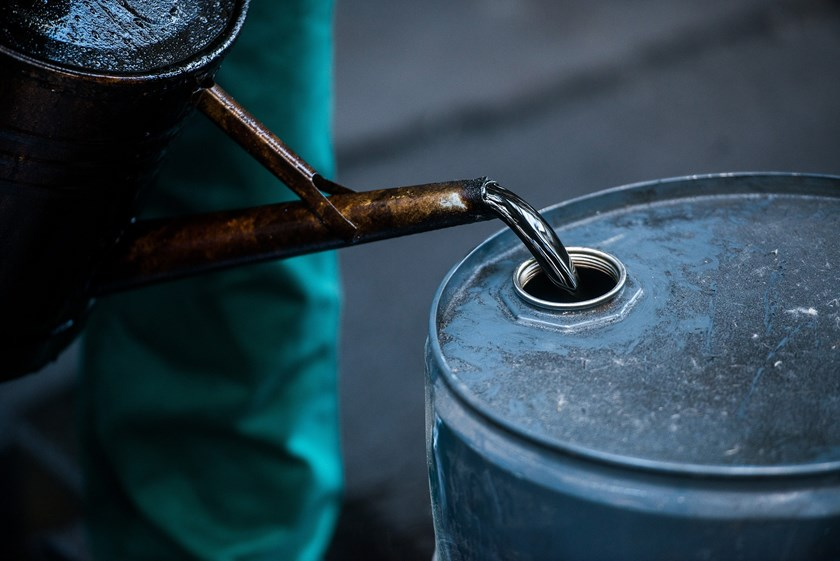 A worker pours liquid oil into a barrel at the delayed coker unit of the Duna oil refinery operated by MOL Hungarian Oil and Gas Plc in Szazhalombatta, Hungary, on Tuesday, July 9, 2013.