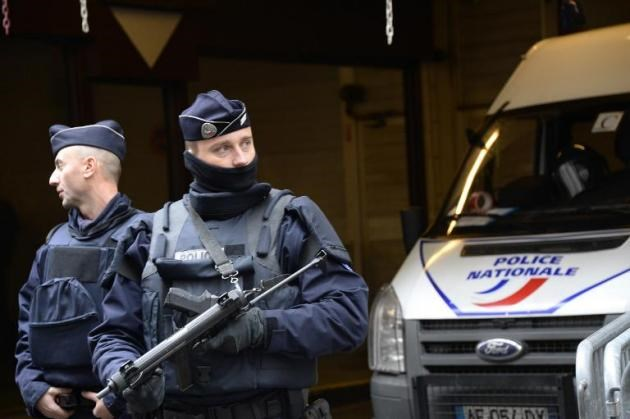 French police officers stand guard in front of the headquarters of French newspaper Liberation in Paris, on January 9, 2015
