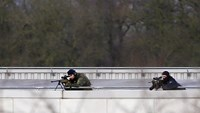 Snipers lie on the top of a building as police close in on Paris terror suspects in Dammartin-en-Goele, northeast of Paris, on Jan. 2015.