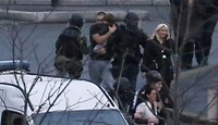 French police special forces evacuate hostages including a child (C) after launching an assault at a kosher grocery store in Porte de Vincennes, eastern Paris, on January 9, 2015