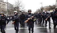 French police officers arrive to take up positions near Porte de Vincennes in Paris today.